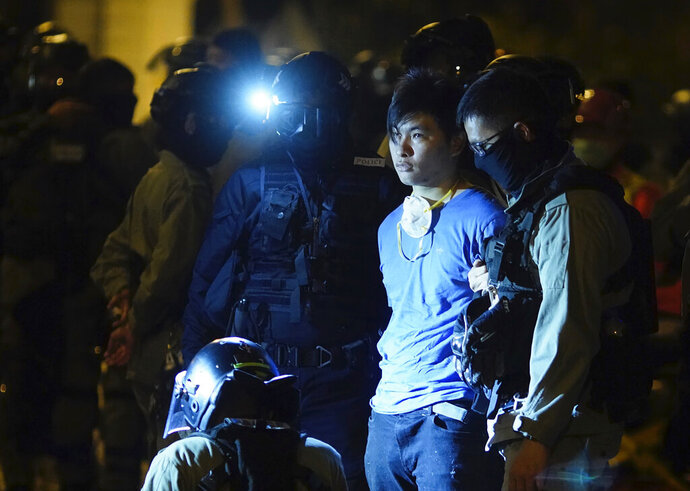Riot police detain a protestor after he tried to escape from Hong Kong Polytechnic University in Hong Kong, Tuesday, Nov. 19, 2019. About 100 anti-government protesters remained holed up at a Hong Kong university Tuesday, their choices dwindling along with their food supplies as they braced for the endgame in a police siege of the campus that entered its third day. (AP Photo/Vincent Yu)