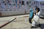 """Women walk past electoral posters in Ain Ouessara, 190 kilometers (118 miles) from Algiers, Thursday, June 10, 2021. In addition to the traditional parties, dozens of independent candidates have decided to take part in the legislative elections on June 12, that the government organized earlier than expected under a new system meant to weed out corruption and open voter rolls — a major step in President Abdelmadjid Tebboune's promise of a """"new Algeria."""" (AP Photo/Fateh Guidoum)"""
