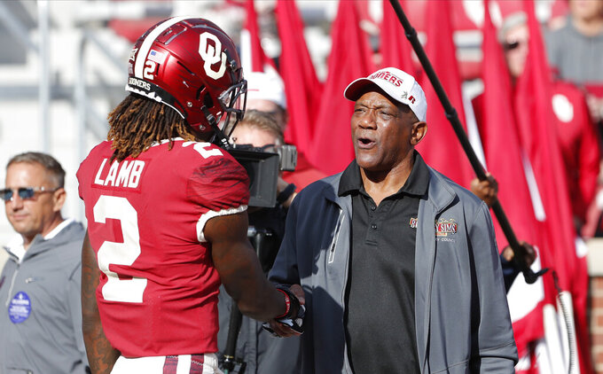 Billy Sims, right, speaks with Oklahoma wide receiver CeeDee Lamb (2) before the start of an NCAA college football game against West Virginia in Norman, Okla., Saturday, Oct. 19, 2019. (AP Photo/Alonzo Adams)