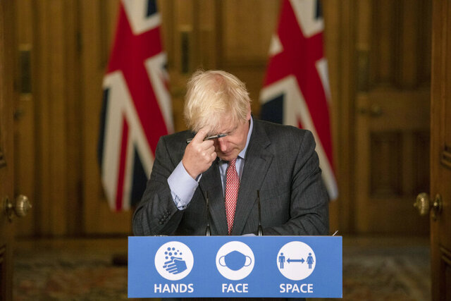 Britain's Prime Minister Boris Johnson gestures, during a coronavirus briefing in Downing Street, London,  Wednesday, Sept. 30, 2020.  The number of new hospitalizations for COVID-19 and virus deaths in Britain are rising again, although both remain far below their springtime peak. (Jack Hill/Pool Photo via AP)