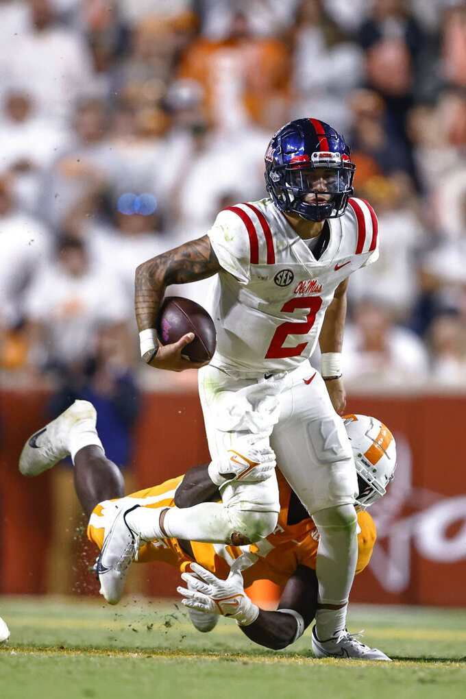 Mississippi quarterback Matt Corral (2) runs for yardage tries to get away from Tennessee linebacker Byron Young (6) during the second half of an NCAA college football game Saturday, Oct. 16, 2021, in Knoxville, Tenn. (AP Photo/Wade Payne)