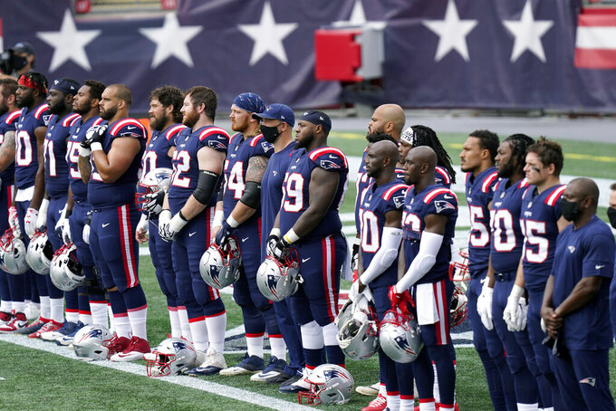 "New England Patriots stand during the singing of ""Lift Every Voice and Sing"" before an NFL football game against the Miami Dolphins, Sunday, Sept. 13, 2020, in Foxborough, Mass. (AP Photo/Steven Senne)"
