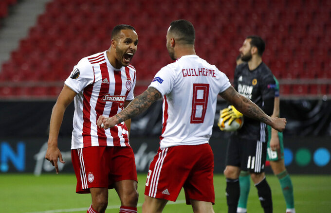 FILE - In this Thursday, March 12, 2020 file photo, Olympiakos' Youssef El-Arabi, left, celebrates with Guilherme after scoring his side's opening goal during the Europa League round of 16 first leg soccer match between Olympiakos and Wolverhampton Wanderers at the Karaiskakis Stadium in Piraeus, Greece. Soccer restarts in Greece this weekend with the fierce rivalry between a runaway league leader and defending champion playing out on the field and in a court in Switzerland. Unbeaten Olympiakos travels to second-place PAOK on Sunday June 4, 2020, in the first Super League championship round _ a new, 10-round playoff for the top six in the regular season table. (AP Photo/Thanassis Stavrakis, File)