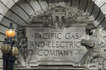 FILE - In this Oct. 10, 2019, file photo, a Pacific Gas & Electric sign is shown outside of a PG&E building in San Francisco. Pacific Gas & Electric plans to bury 10,000 miles of its power lines in an effort to prevent its fraying grid from sparking wildfires when electrical equipment collides with millions of trees and other vegetation sprawling across its drought-stricken service. (AP Photo/Jeff Chiu, File)