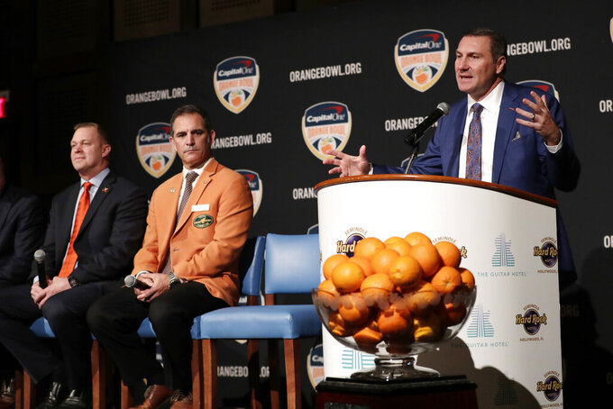 Florida head coach Dan Mullen, right, speaks as Virginia head coach Bronco Mendenhall, left, listens during a news conference for the Orange Bowl NCAA college football game, Wednesday, Dec. 11, 2019, in Hollywood, Fla. Florida plays Virginia in the Orange Bowl Dec. 30 at Hard Rock Stadium in Miami Gardens, Fla. At center is Orange Bowl Committee President Jose Romano. (AP Photo/Lynne Sladky)