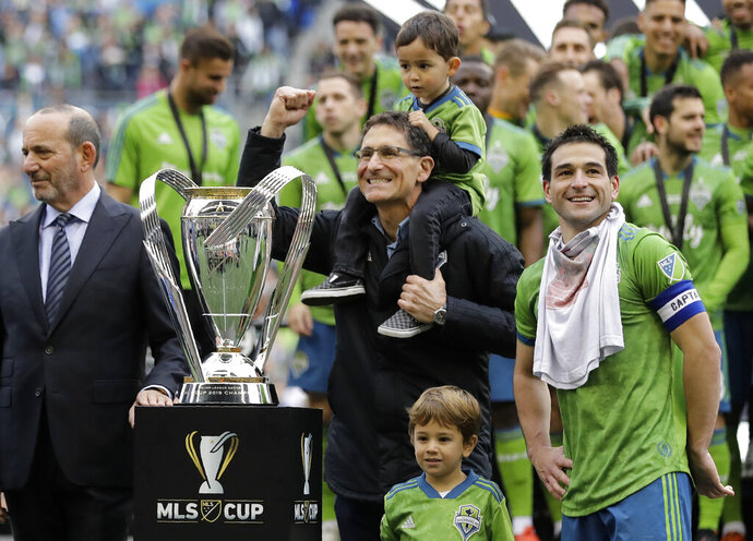 Seattle Sounders owner Adrian Hanauer, center, celebrates beside MLS commissioner Don Garber, left, and player Nicolas Lodeiro, right, after the Sounders defeated Toronto FC, Sunday, Nov. 10, 2019, in the MLS Cup championship soccer match in Seattle. The Sounders won 3-1. (AP Photo/Ted S. Warren)