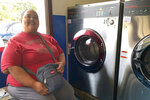Antoninette Arriola does her laundry at a laundromat in the village of Mangilao, Guam as part of her storm preparations on Thursday, Feb. 21, 2019.  An intensifying tropical storm in the Pacific is bearing down on Micronesia and could threaten the U.S. territory of Guam in the coming days.  (AP Photo/Grace Garces Bordallo)