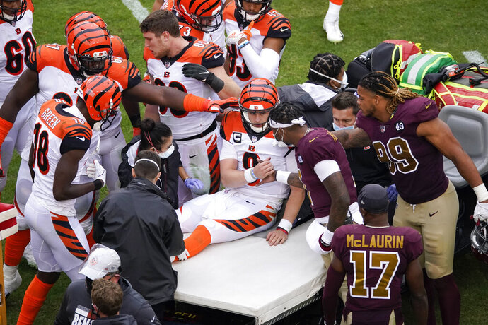 Cincinnati Bengals quarterback Joe Burrow (9) shakes hands with Washington Football Team quarterback Dwayne Haskins (7) as Burrows is carted away off the field during the second half of an NFL football game, Sunday, Nov. 22, 2020, in Landover. Burrows left the game with a left knee injury. (AP Photo/Al Drago)