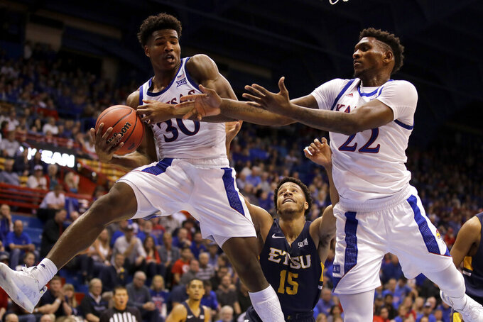Kansas guard Ochai Agbaji (30) and forward Silvio De Sousa (22) beat East Tennessee State guard Isaiah Tisdale (15) to a rebound during the second half of an NCAA college basketball game Tuesday, Nov. 19, 2019, in Lawrence, Kan. Kansas won 75-63. (AP Photo/Charlie Riedel)