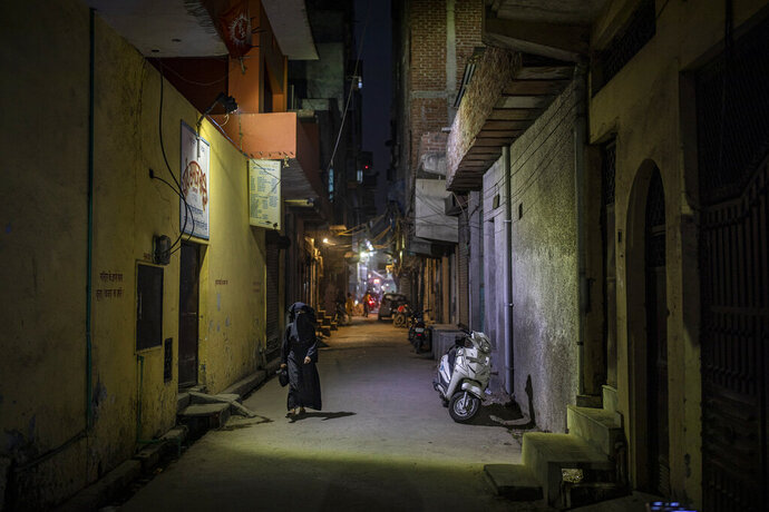 A burqa clad Muslim woman walks in an alleyway in North Ghonda neighborhood, one of the worst riot affected area during the February 2020 communal riots, in New Delhi, India, Friday, Feb. 19, 2021. As the first anniversary of bloody communal riots that convulsed the Indian capital approaches, Muslim victims are still shaken and struggling to make sense of their struggle to seek justice. (AP Photo/Altaf Qadri)