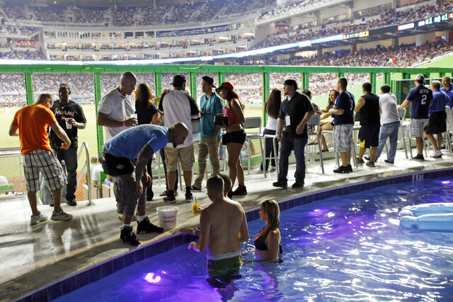 FILE - In this April 2, 2012 file photo fans watch from the swimming pool at Marlins Park during a spring training baseball game between the Miami Marlins and the New York Yankees in Miami. The Clevelander nightclub at Marlins Park has closed. It included a swimming pool, dancers and DJs, and had been a staple at the ballpark since it opened in 2012. The space will still be accessible to fans with different seating and without the pool, but the bar remains. Marlins Park has undergone a gradual makeover since Derek Jeter's group bought the team in late 2017. Before the 2019 season, Jeter removed the kitschy home run sculpture from the outfield. (AP Photo/Wilfredo Lee, file)
