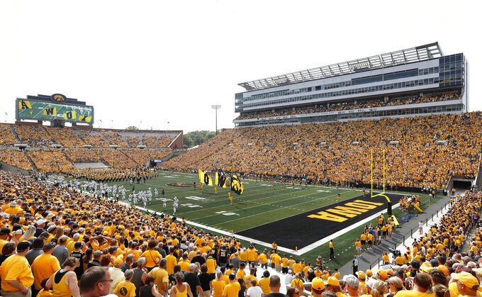 FILE - Fans cheer before an NCAA college football game between Iowa and North Texas at Kinnick Stadium in Iowa City, Iowa, in this Saturday, Sept. 16, 2017, file photo. Iowa will expand alcohol sales at Kinnick Stadium and its other athletic venues as part of a pilot program beginning this fall, the athletic department announced Thursday, June 10, 2021. (AP Photo/Charlie Neibergall, File)