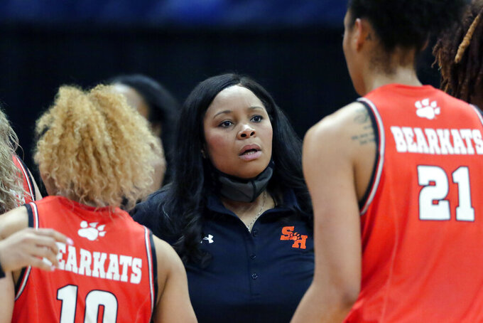 Sam Houston State head coach Ravon Justice talks with her players during the first half of an NCAA college basketball game against Stephen F. Austin for the Southland Conference women's tournament championship Sunday, March 14, 2021, in Katy, Texas. (AP Photo/Michael Wyke)
