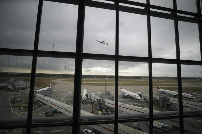 British Airways planes sit parked as a Turkish Airways plane takes off above them at Heathrow Airport in London, Monday, Sept. 9, 2019. British Airways says it has had to cancel almost all flights as a result of a pilots' 48-hour strike over pay. (AP Photo/Matt Dunham)