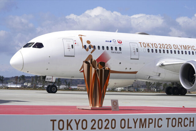 A plane carrying the Olympic flame arrives before Olympic Flame Arrival Ceremony at Japan Air Self-Defense Force Matsushima Base in Higashimatsushima in Miyagi Prefecture, north of Tokyo, Friday, March 20, 2020. The Olympic flame from Greece is set to arrive in Japan even as the opening of the the Tokyo Games in four months is in doubt with more voices suggesting the games should to be postponed or canceled because of the worldwide virus pandemic. (AP Photo/Eugene Hoshiko)