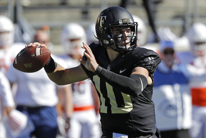 Wake Forest's Sam Hartman (10) looks to pass against Syracuse in the first half of an NCAA college football game in Charlotte, N.C., Saturday, Nov. 3, 2018. (AP Photo/Chuck Burton)