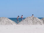 This Monday,  June 8, 2020 photo shows boys playing on large piles of sand stacked up on the beach in North Wildwood, N.J. On June 6, 2020, the New Jersey Department of Environmental Protection said North Wildwood had demolished dunes and wetlands, built a sea wall and added buildings to a pier without required permits or review by the agency, which may make the city tear the work it did, and restore the area to its natural condition. (AP Photo/Wayne Parry)