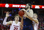 Illinois' Giorgi Bezhanishvili, center, grabs an offensive rebound against Wisconsin's Ethan Happ, left, and Brad Davison, right, during the first half of an NCAA college basketball game Monday, Feb. 18, 2019, in Madison, Wis. (AP Photo/Andy Manis)