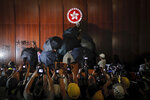 FILE - In this file photo taken Monday, July 1, 2019, journalists film a protester about to deface the Hong Kong emblem inside the meeting hall of the Legislative Council in Hong Kong, Protesters in Hong Kong took over the legislature's main building Monday night, tearing down portraits of legislative leaders and spray painting pro-democracy slogans on the walls of the main chamber. (AP Photo/Kin Cheung, File)