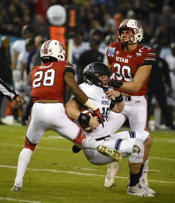 Northwestern quarterback Clayton Thorson (18) is sacked for a 10-yard loss by Utah defensive back Javelin K. Guidry (28) and linebacker Cody Barton (30) during the first half of the Holiday Bowl NCAA college football game Monday, Dec. 31, 2018, in San Diego. (AP Photo/Denis Poroy)