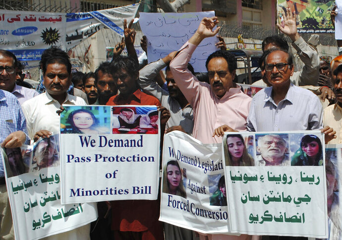 Pakistani civil society activists call for protection of Hindu girls at a protest in Hyderabad, Pakistan, Tuesday, March 26, 2019. A court in Islamabad has ordered protection for two teenage sisters from the minority Hindu community as investigators widen a probe to determine whether the girls were abducted and forced to convert and marry two Muslims. The Islamabad High Court issued the order on Tuesday. Placard at right reads,