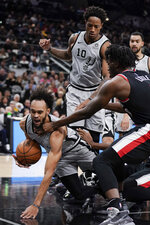 San Antonio Spurs' Derrick White, left, falls after colliding with Portland Trail Blazers' Nassir Little during the first half of an NBA basketball game, Saturday, Nov. 16, 2019, in San Antonio. (AP Photo/Darren Abate)