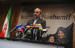 Paiman Jebeli, deputy chief of Iran's state IRIB broadcaster gives a press briefing about American-born news anchor who works on Iranian state television's English-language service, Marzieh Hashemi, shown in banner, in Tehran, Iran, Wednesday, Jan. 16, 2019. Hashemi has been arrested after flying into the U.S., the broadcaster reported Wednesday. The reported detention of Press TV's Hashemi, born Melanie Franklin of New Orleans, comes as Iran faces increasing criticism of its own arrests of dual nationals and others with Western ties, previously used as bargaining chips in negotiations with world powers. (AP Photo/Vahid Salemi)
