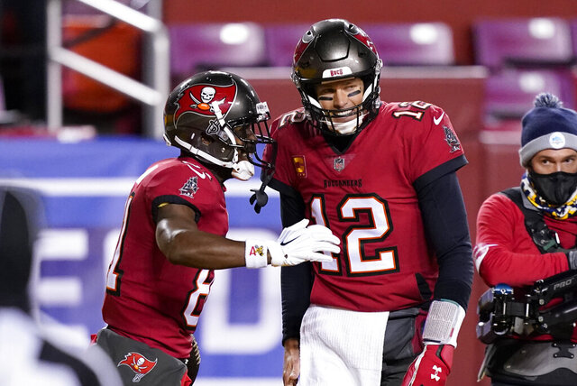 Tampa Bay Buccaneers wide receiver Antonio Brown (81) celebrates his touchdown with quarterback Tom Brady (12) during the first half of an NFL wild-card playoff football game against the Washington Football Team, Saturday, Jan. 9, 2021, in Landover, Md. (AP Photo/Andrew Harnik)