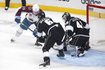 Los Angeles Kings goaltender Calvin Petersen, right, blocks a shot by Colorado Avalanche left wing Matt Calvert, left, during the first period of an NHL hockey game Tuesday, Jan. 19, 2021, in Los Angeles. (AP Photo/Kyusung Gong)