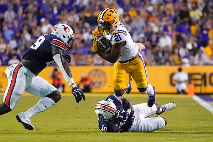 LSU running back Corey Kiner (21) carries against Auburn safety Zion Puckett (10) and safety Bydarrius Knighten (19) during the first half of an NCAA college football game in Baton Rouge, La., Saturday, Oct. 2, 2021. (AP Photo/Gerald Herbert)