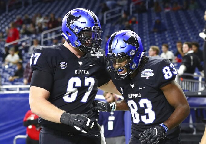 Buffalo wide receiver Anthony Johnson (83) is congratulated by offensive lineman Evin Ksiezarczyk (67) after scoring on a 13-yard pass for a touchdown during the first half of the Mid-American Conference championship NCAA college football game against Northern Illinois, Friday, Nov. 30, 2018, in Detroit. (AP Photo/Carlos Osorio)