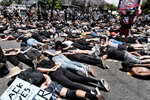 LGBTQ community members join Black Lives Matter protesters as they block an intersection laying on the street with their hands behind their backs in West Hollywood, Calif. on Wednesday, June 3, 2020, over the death of George Floyd. Floyd, a black man died after being restrained by Minneapolis police officers on May 25. (AP Photo/Richard Vogel)