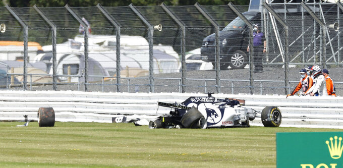 Alpha Tauri driver Daniil Kvyat of Russia stands on the right after crashing during the British Formula One Grand Prix at the Silverstone racetrack, Silverstone, England, Sunday, Aug. 2, 2020. (Andrew Boyers/Pool via AP)