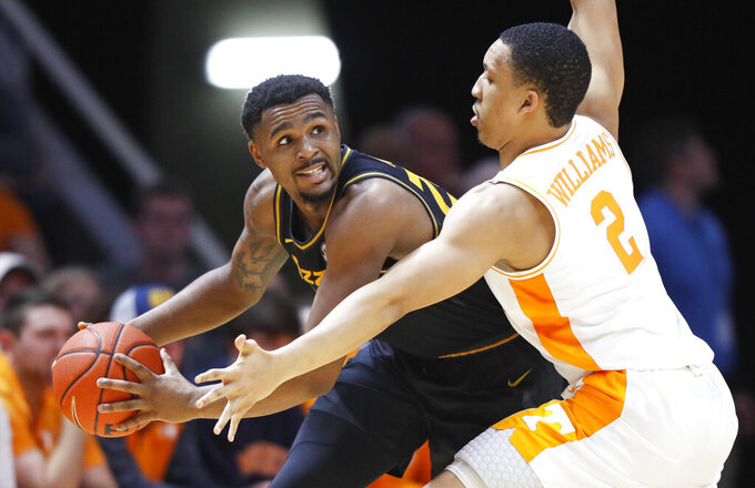 Missouri guard K.J. Santos, left, looks to pass as he's defended by Tennessee forward Grant Williams, right, during the first half of an NCAA college basketball game Tuesday, Feb. 5, 2019, in Knoxville, Tenn. (AP photo/Wade Payne)