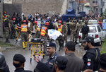 Pakistani volunteers remove a body of alleged terrorist from a militant hideout following a crackdown operation in Peshawar, Pakistan, Tuesday, April 16, 2019. Pakistani authorities say a raid by security forces on a militant hideout in the northwestern city of Peshawar triggered a 15-hour shootout in which a police officer and many suspected militants were killed. (AP Photo/Muhammad Sajjad)