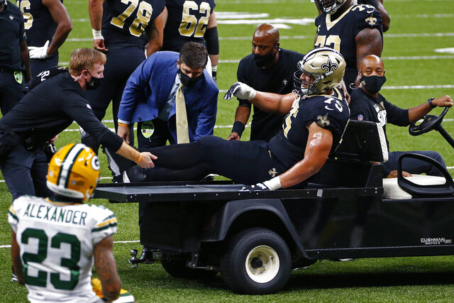 New Orleans Saints offensive guard Andrus Peat (75) is tended to after being injured in the first half of an NFL football game against the Green Bay Packers in New Orleans, Sunday, Sept. 27, 2020. (AP Photo/Butch Dill)