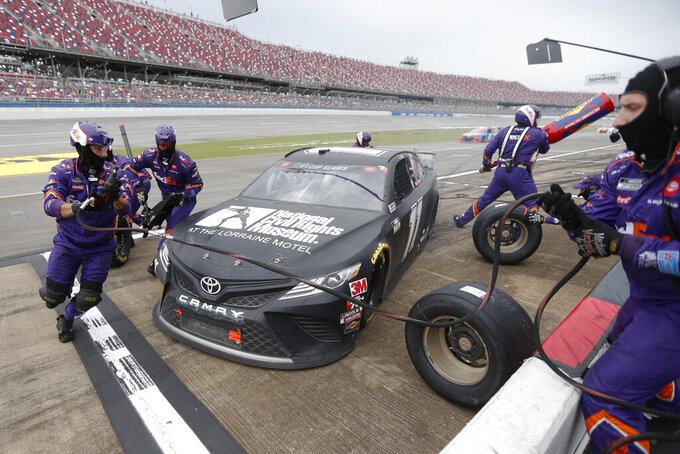 Denny Hamlin (11) gets service in the pits during a NASCAR Cup Series auto race at Talladega Superspeedway in Talladega Ala., Monday, June 22, 2020. (AP Photo/John Bazemore)