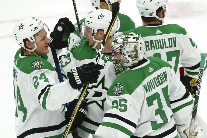 Dallas Stars goaltender Anton Khudobin (35) celebrates a win against the Arizona Coyotes with Stars left wing Roope Hintz (24), defenseman Esa Lindell (23) and right wing Alexander Radulov (47) as time expires in an NHL hockey game, Sunday, Dec. 29, 2019, in Glendale, Ariz. The Stars defeated the Coyotes 4-2. (AP Photo/Ross D. Franklin)