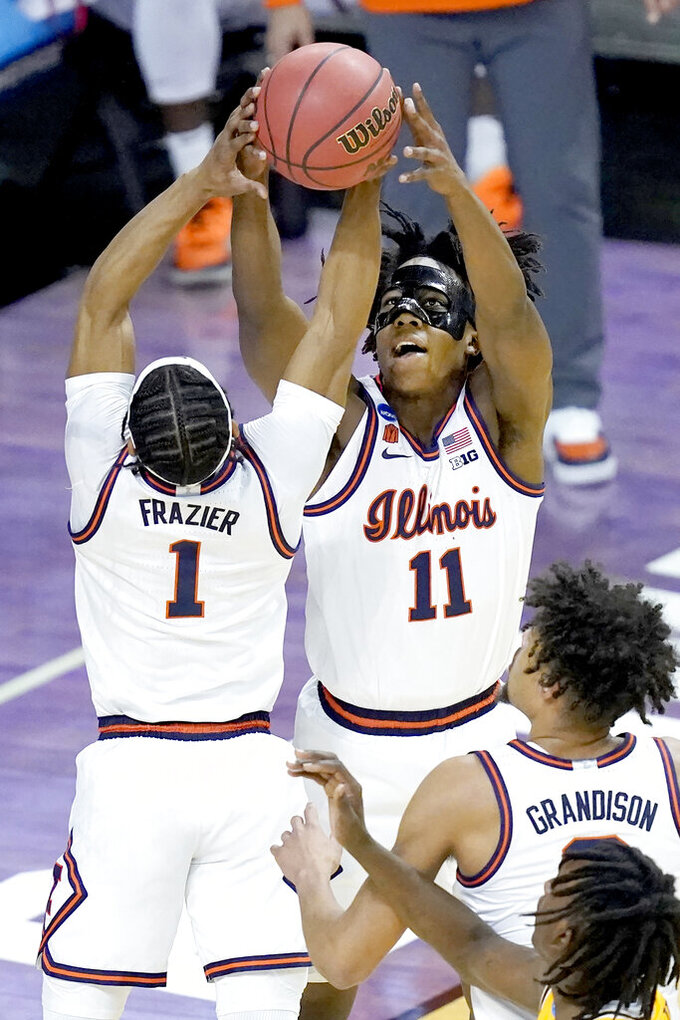 Illinois guard Ayo Dosunmu (11) and teammate Trent Frazier reach for a rebound during the first half of a first round NCAA college basketball tournament game Friday, March 19, 2021, at the Indiana Farmers Coliseum in Indianapolis .(AP Photo/Charles Rex Arbogast)