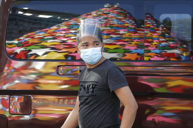 A man wearing a mask to prevent the spread of the coronavirus walks past a reflection of a colorful Christmas tree in Quezon city, Philippines on Tuesday, Nov. 24, 2020. Philippine Officials say about 60 million Filipinos are being targeted for vaccination against the coronavirus next year at a cost of more than 73 billion pesos ($1.4 billion) to develop considerable immunity among a majority of the population. (AP Photo/Aaron Favila)