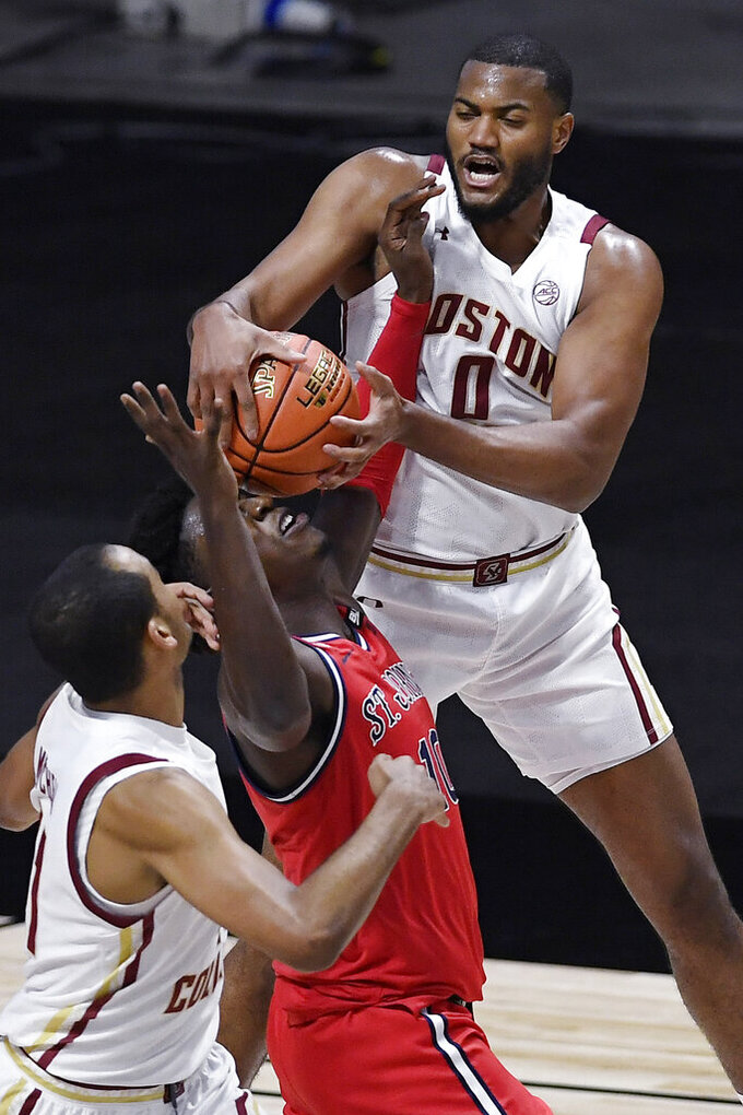 Boston College's Frederick Scott, top, grabs the ball over St. John's Marcellus Earlington, center, as Boston College's Steffon Mitchell, left, looks on in the first half of an NCAA college basketball game, Monday, Nov. 30, 2020, in Uncasville, Conn. (AP Photo/Jessica Hill)