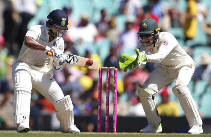 In this Jan. 4, 2019, file photo, India's Rishabh Pant, left, plays a shot in front of Australia's Tim Paine on day 2 during their cricket test match in Sydney. Cricket Australia is considering an expanded five-test series against India next season and is still planning to host the Twenty20 World Cup later this year, even if it has to be staged in empty stadiums. (AP Photo/Rick Rycroft, File)