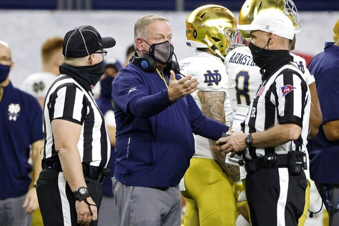 Notre Dame head coach Brian Kelly, center, talks to officials in the first half of the Rose Bowl NCAA college football game against Alabama in Arlington, Texas, Friday, Jan. 1, 2021. (AP Photo/Michael Ainsworth)