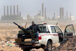 FILE - In this March 5, 2011 file photo, an anti-government rebel sits with an anti-aircraft weapon in front an oil refinery in Ras Lanouf, eastern Libya. The United Nations said Friday, Oct. 23, 2020, that the two sides in Libyan military talks had reached a