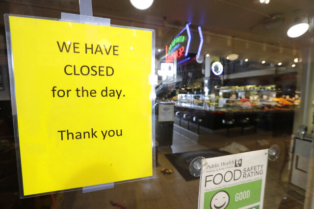 A sign advises of the closure of a restaurant at Pike Place Market on Tuesday, March 17, 2020, in Seattle. Many shops in the landmark market continue to remain open, though business has dropped considerably in recent weeks. A day earlier, Washington Gov. Jay Inslee ordered all bars, restaurants, entertainment and recreation facilities to temporarily close to fight the spread of COVID-19 in the state with by far the most deaths in the Unite States from the disease. (AP Photo/Elaine Thompson)