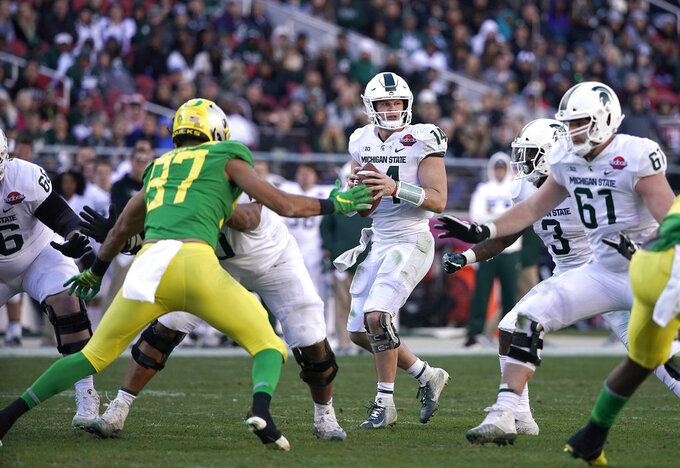 Michigan State quarterback Brian Lewerke (14) drops back to pass against Oregon during the second half of the Redbox Bowl NCAA college football game Monday, Dec. 31, 2018, in Santa Clara, Calif.  (AP Photo/TonyAvelar)