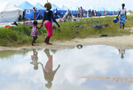 A woman and child are reflected in a puddle as they walk at a camp for displaced survivors of cyclone Idai, in Beira, Mozambique, Tuesday, April, 2, 2019. Mozambican and international health workers raced Monday to contain a cholera outbreak in the cyclone-hit city of Beira and surrounding areas, where the number of cases has jumped to more than 1,000. (AP Photo/Tsvangirayi Mukwazhi)