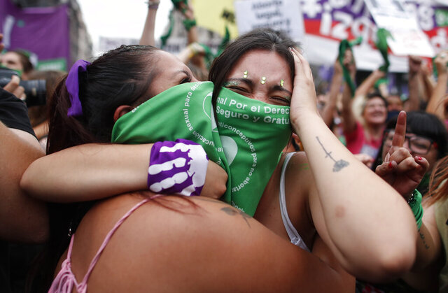 Abortion-rights activists celebrate as Argentine lower house approves a bill that would legalize abortion outside Congress in Buenos Aires, Argentina, Friday, Dec. 11, 2020. The bill now moves to the Senate. (AP Photo/ Natacha Pisarenko)