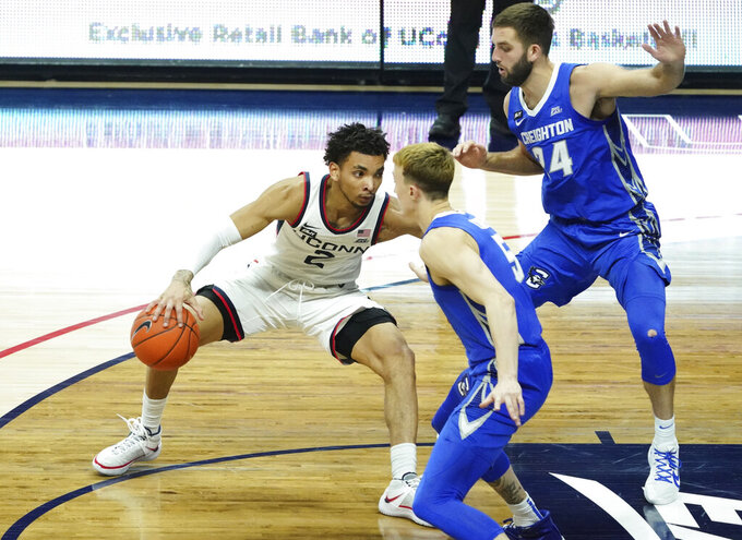 Connecticut guard James Bouknight (2) dribbles against Creighton guards Mitch Ballock (24) and Alex O'Connell (5) in the first half of an NCAA college basketball game in Storrs, Conn., Sunday, Dec. 20, 2020. (David Butler II/Pool Photo via AP)