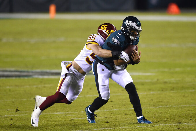 Philadelphia Eagles' Jalen Hurts, right, is tackled by Washington Football Team's Cole Holcomb during the first half of an NFL football game, Sunday, Jan. 3, 2021, in Philadelphia. (AP Photo/Derik Hamilton)